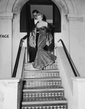 Monroe and Miller leave the theatre. 'How could she walk?' asked the Daily Mail, reporting that the star wore 'a scarlet satin gown so tight around the knees that walking was an achievement'.